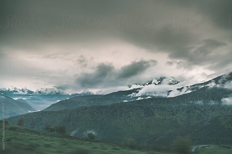 Snowy mountain landscape with clouds from the car by Javier Pardina for Stocksy United