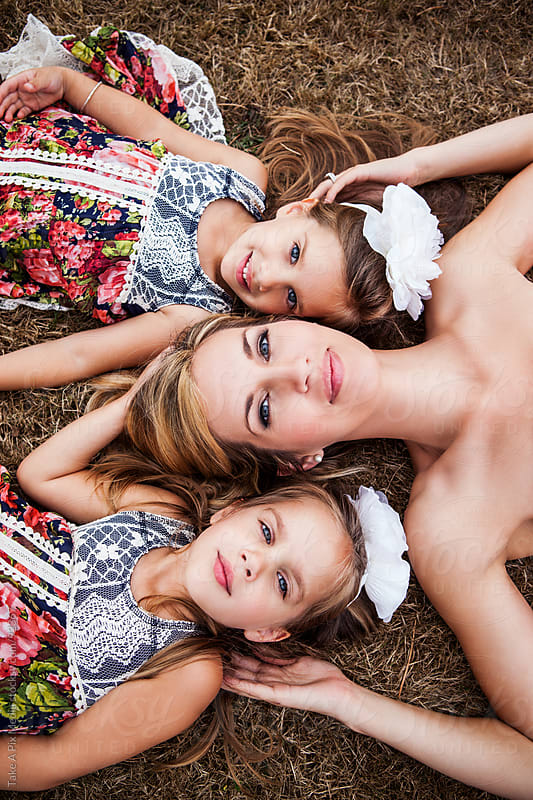 Mother and her twin daughters lying down on the grass by Suprijono Suharjoto for Stocksy United