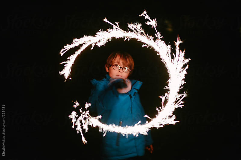Boy with sparkler by Kirstin Mckee for Stocksy United