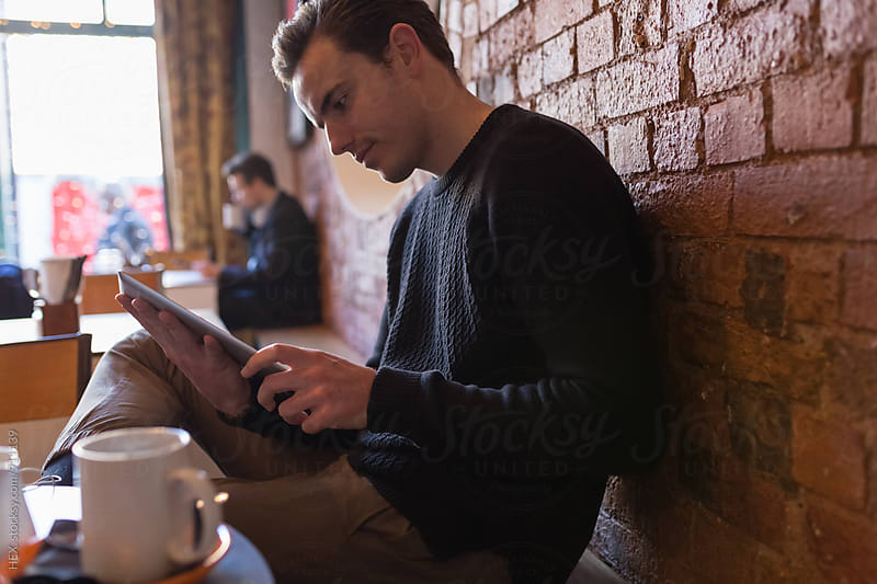 Young Man Using Digital Tablet in a Coffee Shop by HEX . for Stocksy United