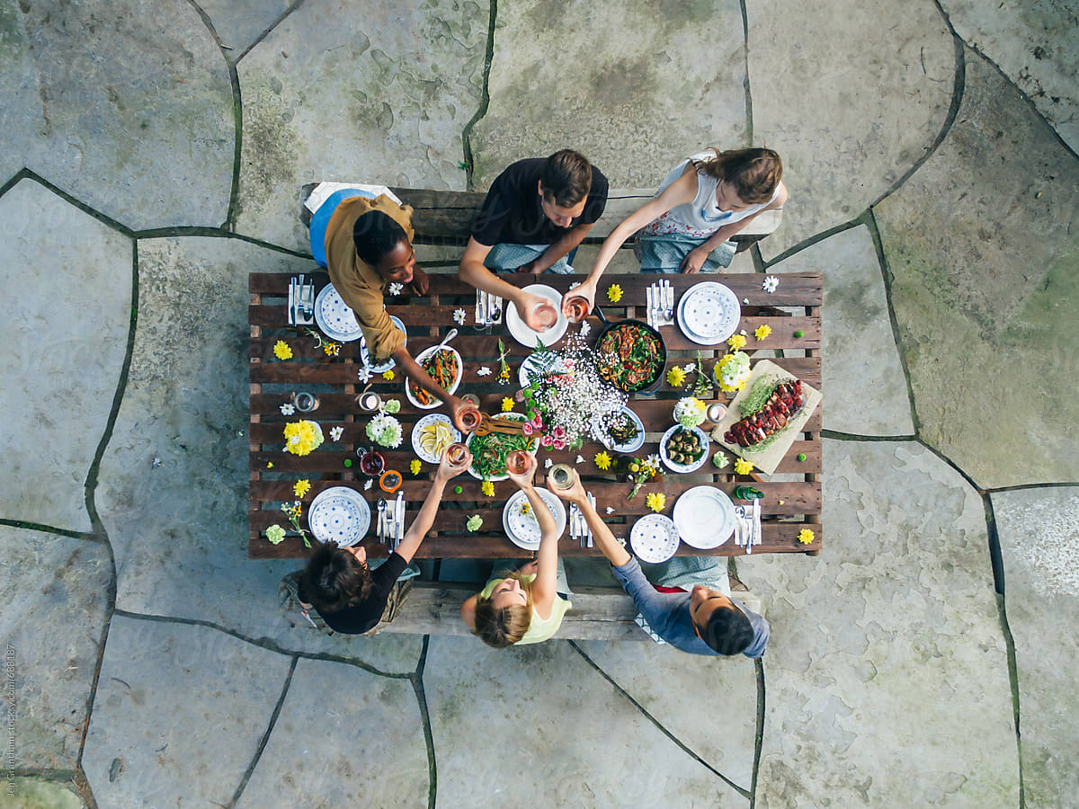 Stock photo of friends toasting with wine at an outdoor summer feast