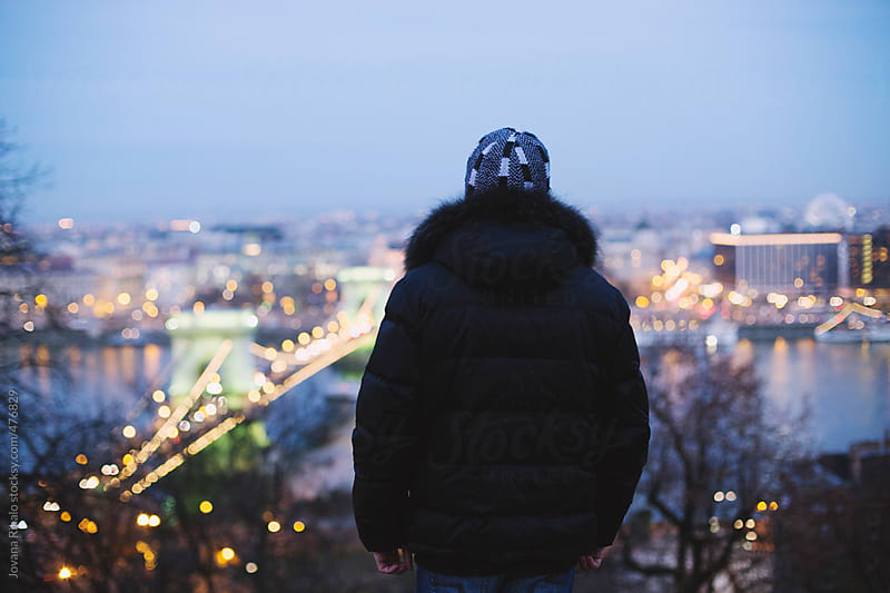 Back view of a man watching city lights by Jovana Rikalo for Stocksy United