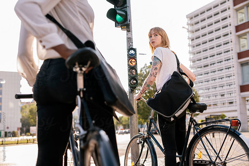 Two Commuters on Bicycles waiting at Stoplight by VegterFoto for Stocksy United