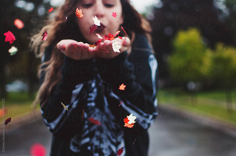 A young woman blowing leaf shaped confetti by Chelsea Victoria for Stocksy United