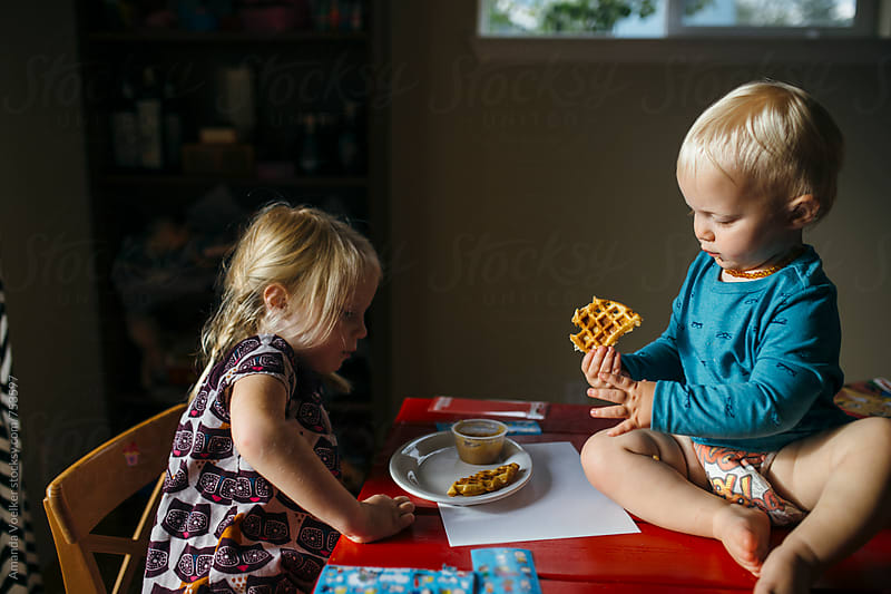 Young girl and her baby brother share a snack by Amanda Voelker for Stocksy United