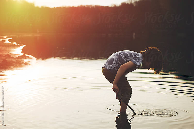 Young Boy Exploring in a River During Sunset by Kevin Keller for Stocksy United