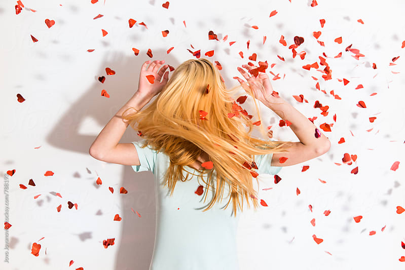 Heart-shaped confetti falling over a blonde girl by Jovo Jovanovic for Stocksy United