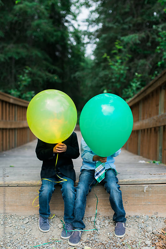 two young boys hide their faces behind balloons by Tara Romasanta for Stocksy United