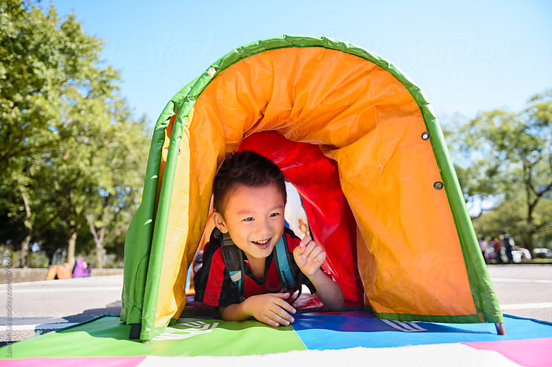 Child leaning in tent tube on parking lot in sunlight by Lawren Lu for Stocksy United