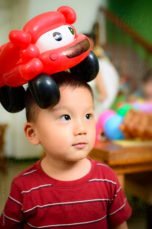A balloon car on boy's head by Lawren Lu for Stocksy United