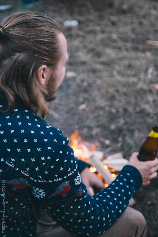 Wanderer drinking beer near bonfire by Danil Nevsky for Stocksy United