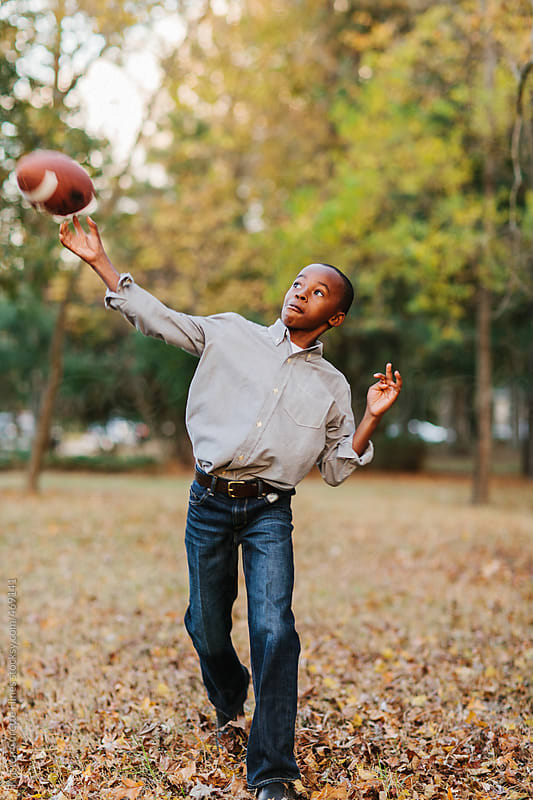 A young African American boy playing catch with a football in a park by Kristen Curette Hines for Stocksy United