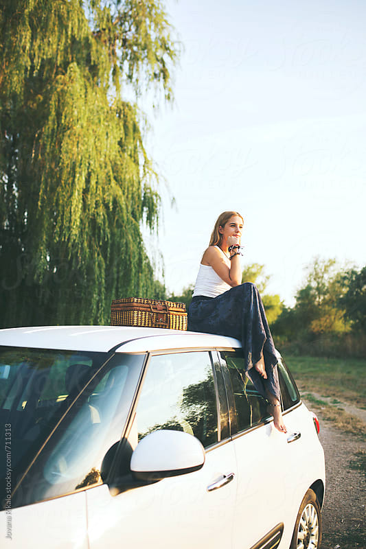 Beautiful young woman sitting on a car and watching sunset by Jovana Rikalo for Stocksy United