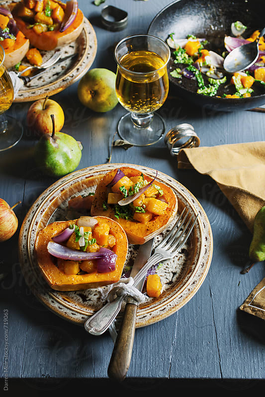 Stuffed squash meals on plates with cider in a rustic table setting.  by Darren Muir for Stocksy United