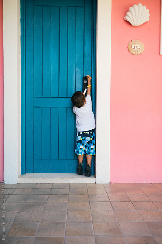 A little boy trying to get into a hotel room at a resort by Emmanuel Hidalgo for Stocksy United