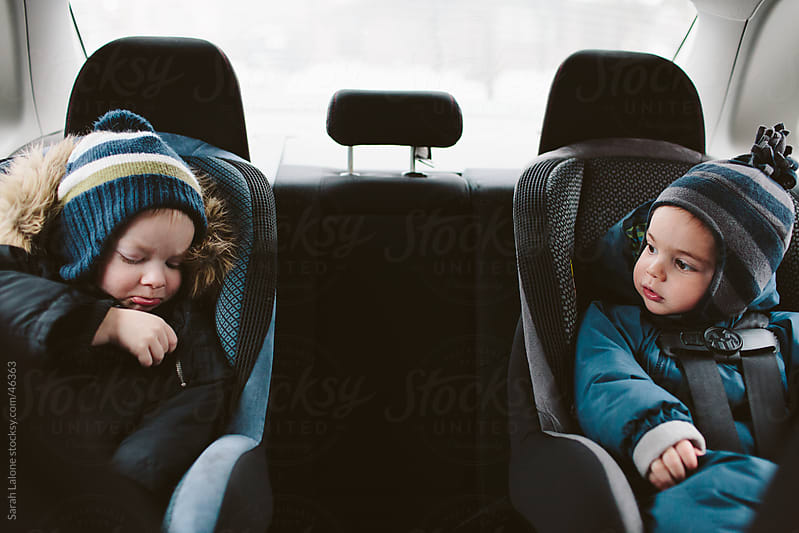 Two little boys in carseats in the their snowsuits by Sarah Lalone for Stocksy United