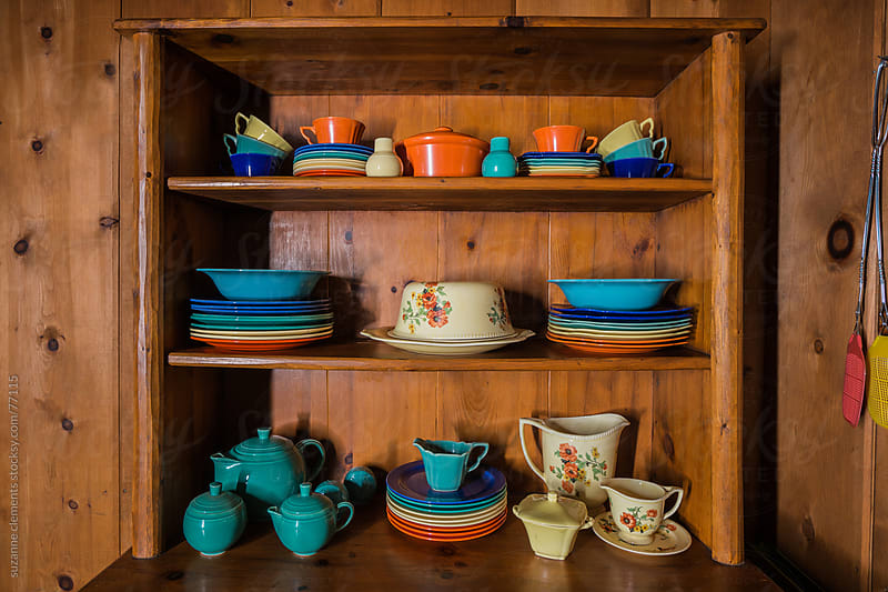 Colorful Antique Dishes in a Wooden Hutch by suzanne clements for Stocksy United