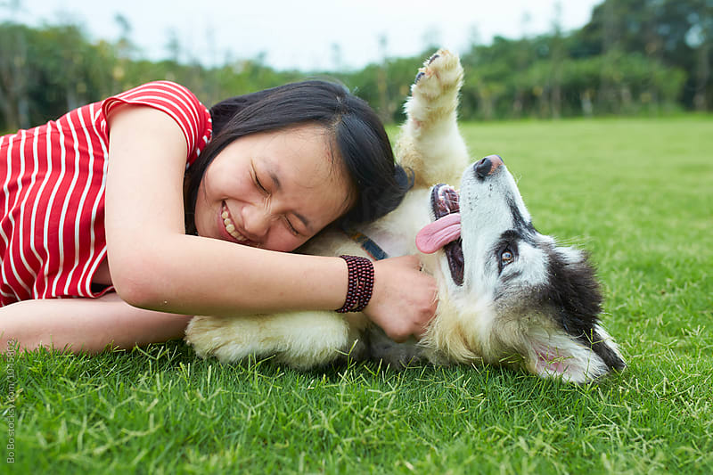 lovely young woman having fun with her dog on the lawn by cuiyan Liu for Stocksy United