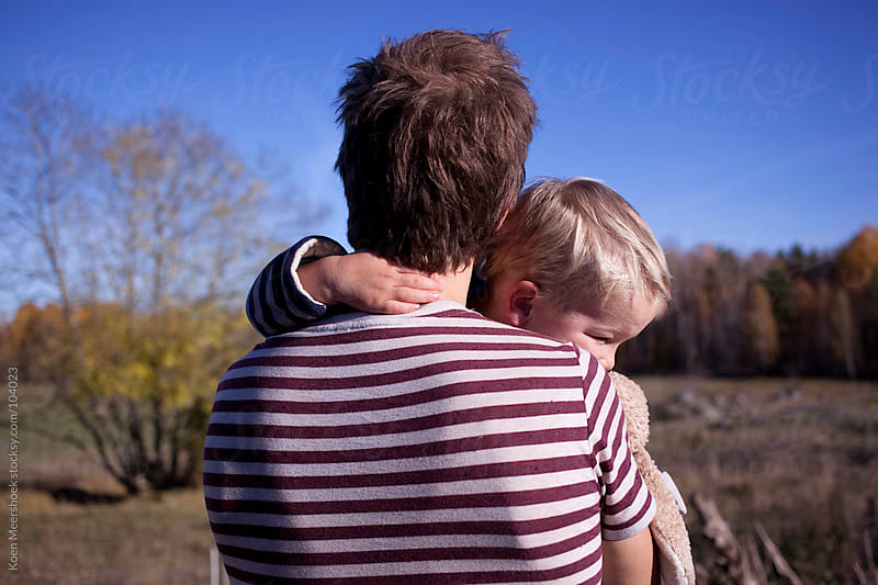 A dad holding his little boy and looking to the forest. by Koen Meershoek for Stocksy United