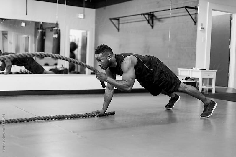 Fit and muscular african american athlete working out with exercise ropes by Jakob for Stocksy United