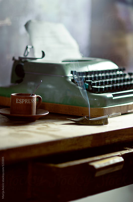 Vintage retro typewriter with cup of coffee and cigarette on wooden desk by Marija Anicic for Stocksy United