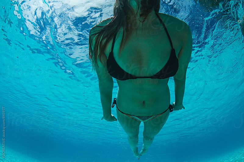 Woman swimming underwater. by Robert Zaleski for Stocksy United