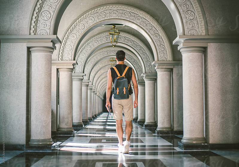 Young man walking through long hallway.  by Jovo Jovanovic for Stocksy United