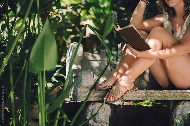 Girl reading in the Garden by Aila Images for Stocksy United
