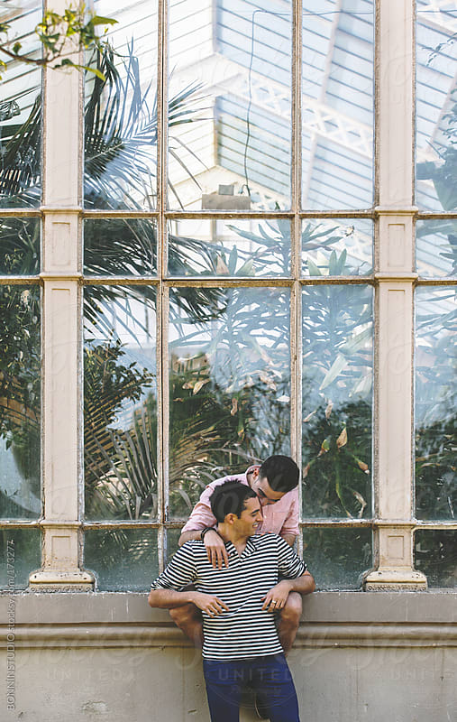 Young gay couple talking in front a greenhouse.  by BONNINSTUDIO for Stocksy United
