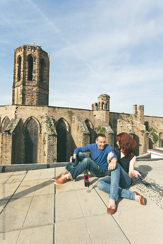 Beautiful couple drinking wine and having fun on the rooftop in front a romanic church. by BONNINSTUDIO for Stocksy United
