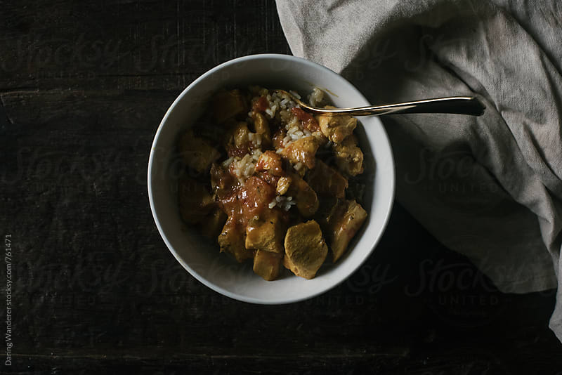 Curry chicken and rice in bowl styled on dark wood table by Daring Wanderer for Stocksy United