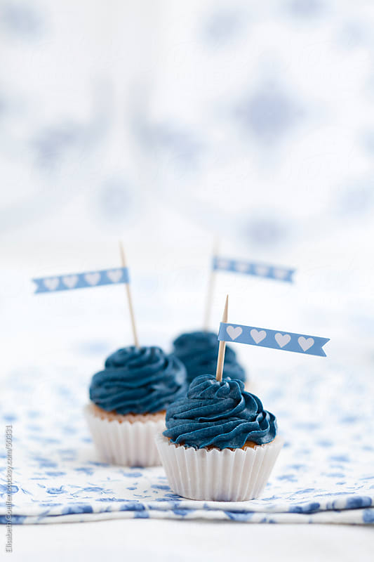Three mini cupcakes with blue cream cheese frosting and cupcake toppers by Elisabeth Coelfen for Stocksy United