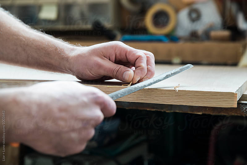 Carpenter hands using a file to finish a piece of wood by Lior + Lone for Stocksy United