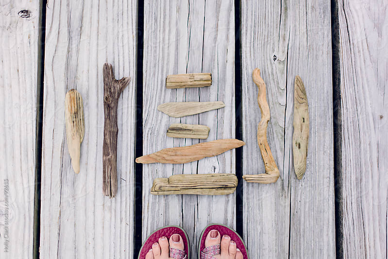 A woman's feet standing on a dock next to driftwood. by Holly Clark for Stocksy United