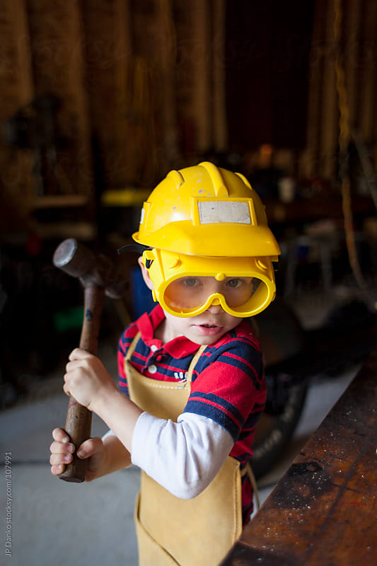 Little Boy in Garage Working with Hammer and Nails by JP Danko for Stocksy United
