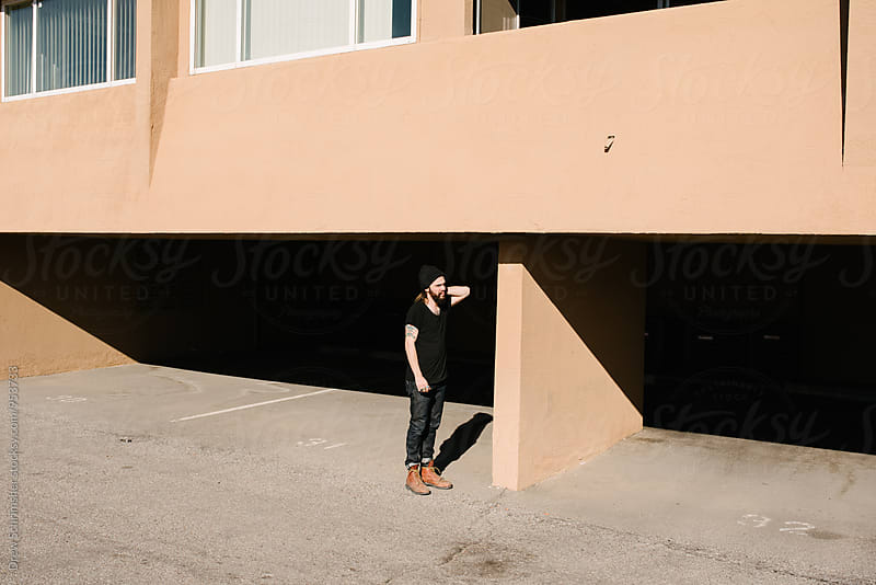 Young man stands outside adobe building  by Drew Schrimsher for Stocksy United