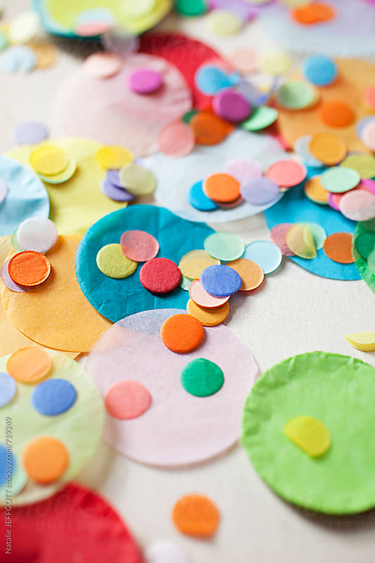close up of colourful confetti on a ply wood table top by Natalie JEFFCOTT for Stocksy United