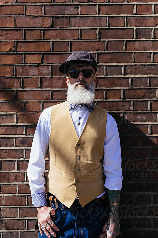 Eccentric Stylish Man Portrait Against a Brick Wall by HEX. for Stocksy United