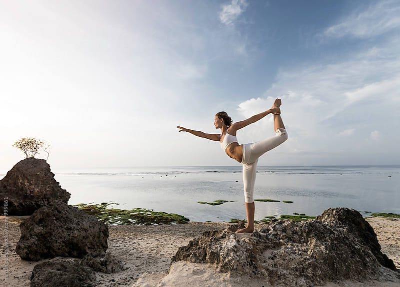 young woman practicing yoga on the beach by martin puddy for Stocksy United