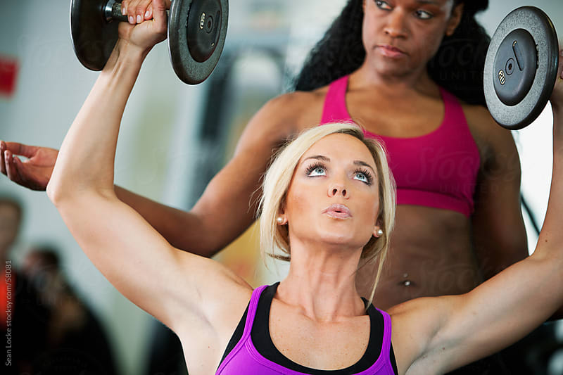 Gym: Strong Woman Lifting Weights with Spotter by Sean Locke for Stocksy United