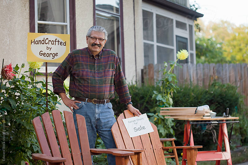 A home craftsman selling his handmade adirondack chairs at home by Edward Bock for Stocksy United
