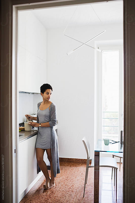 African young woman at home in the kitchen by michela ravasio for Stocksy United