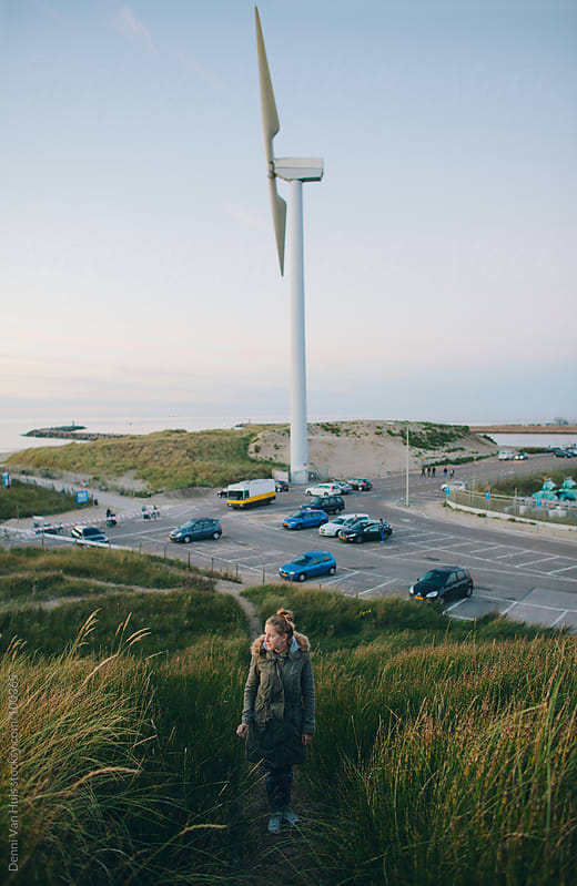 Woman on a dune standing in front of a windmill  by Denni Van Huis for Stocksy United