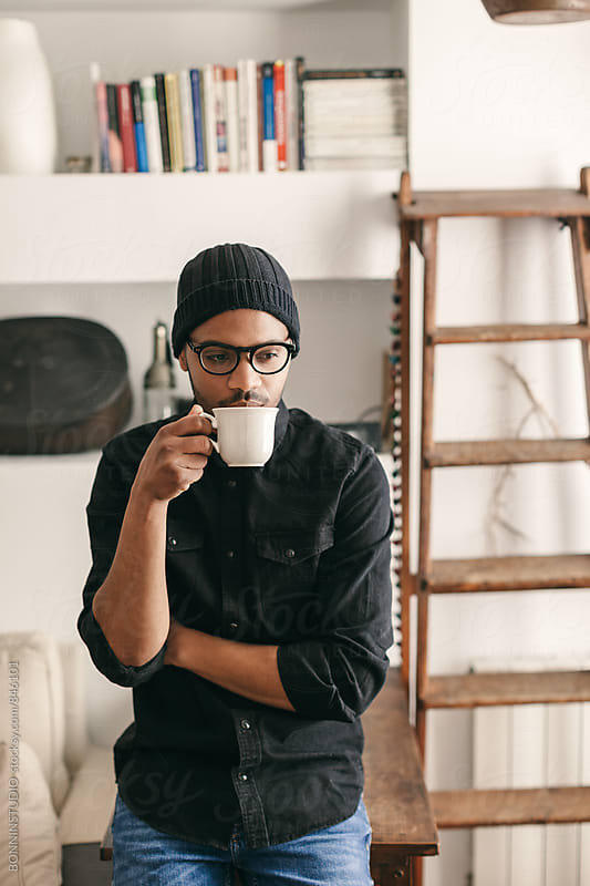 Portrait of a latin man drinking a cup of coffee at home. by BONNINSTUDIO for Stocksy United