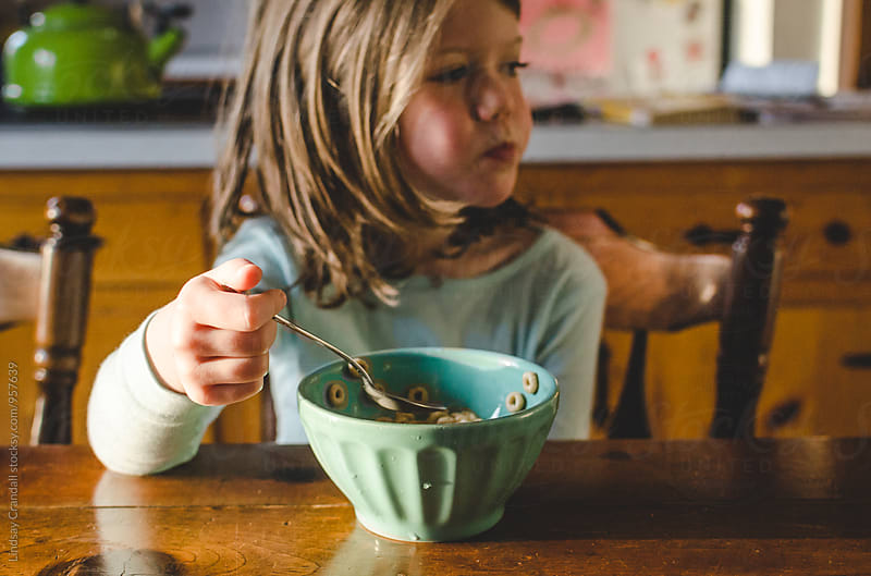 Girl eating a bowl of cereal by Lindsay Crandall for Stocksy United