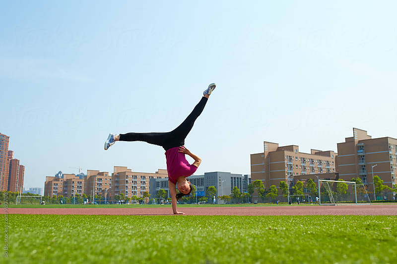 one young asian woman doing handstand outdoor by Bo Bo for Stocksy United