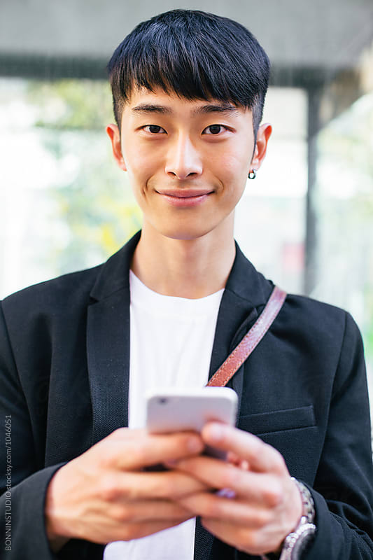 Portrait of a young asian businessman using his phone outside.  by BONNINSTUDIO for Stocksy United