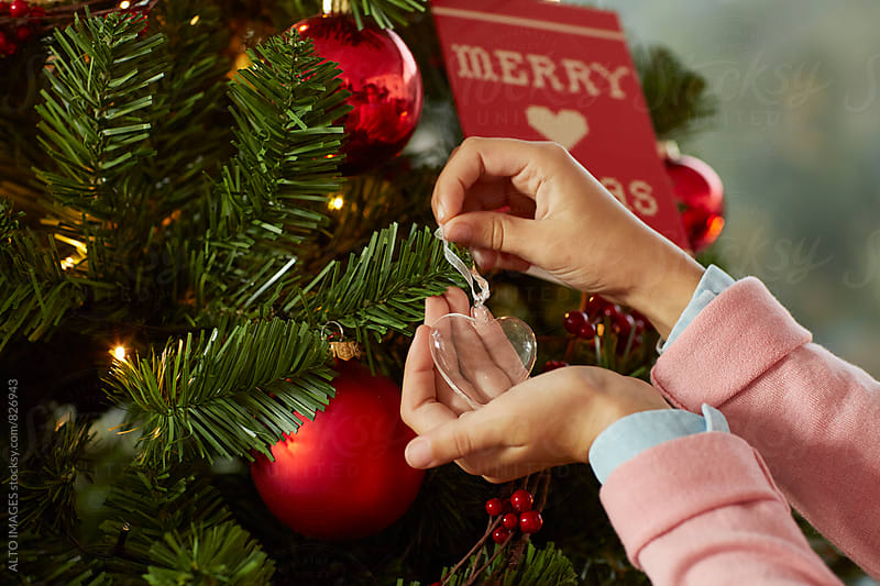 Girl Hanging Heart Shaped Ornament On Christmas Tree by ALTO IMAGES for Stocksy United