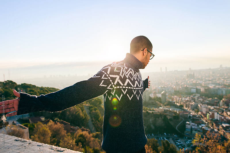 Young latin man enjoying a sunny winter day above Barcelona. by BONNINSTUDIO for Stocksy United