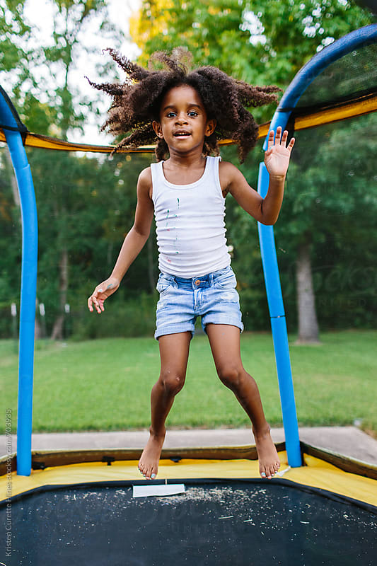 A young African American girl jumping on her trampoline outside by Kristen Curette Hines for Stocksy United